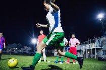 Молодые футболистки играют в футбол на поле ночью, пинают мяч — стоковое фото