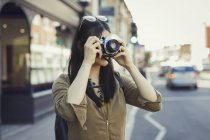 Young female tourist photographing with camera on urban street — Stock Photo