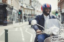Smiling young businessman in helmet riding motor scooter on urban street — Stock Photo