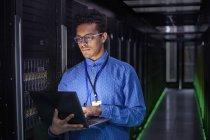 Focused male IT technician using laptop in dark server room — Stock Photo