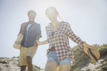 Sorrindo, casal multi-étnico afetuoso de mãos dadas andando no ensolarado verão areia praia caminho — Fotografia de Stock