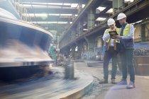 Мужчина бригадир и инженер с цифровой планшет говорить на заводе — стоковое фото