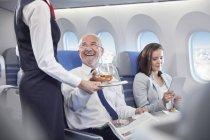 Assistente di volo che serve whisky a un uomo d'affari sorridente che guida in prima classe in aereo — Foto stock