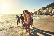 Playful young friends walking in sunny summer ocean surf — Stock Photo