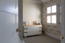 Illuminated string light star on dresser in child?s bedroom — Stock Photo