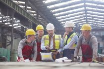 Male foreman, engineers and workers meeting in factory — Stock Photo