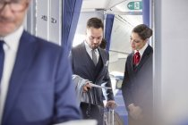 Flight attendant helping businessman with boarding pass on airplane — Stock Photo