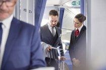 Стюардеса допомагають бізнесмен з посадковий талон на літак — стокове фото