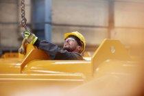 Мужчина прикрепляет цепь к оборудованию на заводе — стоковое фото
