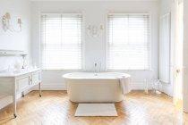 White, luxury home showcase bathroom with soaking tub and parquet hardwood floor — Stock Photo