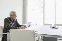 Senior businessman reviewing paperwork in conference room — Stock Photo