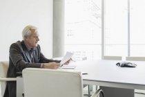 Leitenden Geschäftsmann Überprüfung Papierkram im Konferenzraum — Stockfoto