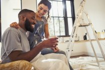 Affectionate young couple drinking coffee and painting living room — Stock Photo