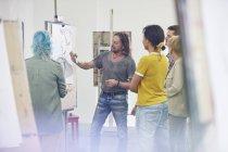Étudiants écoutant un instructeur dessiner au chevalet dans un studio de classe d'art — Photo de stock
