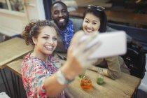 Улыбающиеся юные друзья делают селфи с камерой телефона в кафе на тротуаре — стоковое фото