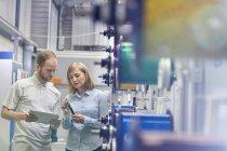 Männliche und weibliche Vorgesetzte mit digitalem Tablet, das Glasfaserkabel in der Fabrik inspiziert — Stockfoto