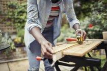 Frau mit Maßband misst Holz auf Terrasse — Stockfoto