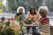 Freundinnen reden und Essen im café — Stockfoto