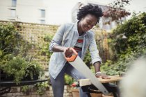 Woman with saw cutting wood — Stock Photo
