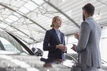 Car saleswoman talking to male customer in car dealership showroom — Stock Photo