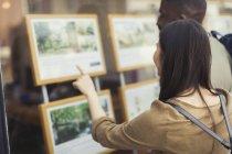Jeune couple parcourant annonces immobilières à devanture — Photo de stock