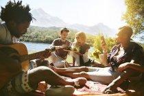 Молодих друзів гуляти, грав на гітарі і насолоджуючись пікнік на березі річки Сонячний літній — стокове фото