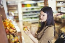 Young woman shopping, examining apple in grocery store — Stock Photo