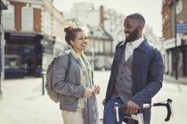 Smiling couple commuting with bicycle on sunny urban street — Stock Photo