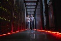 IT technicians talking and walking in dark server room — Stock Photo