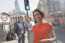 Portrait smiling businesswoman on sunny urban city street, London, UK — Stock Photo