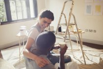 Affectionate young couple painting living room — Stock Photo