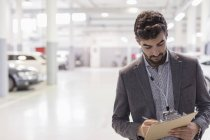 Car salesman writing on clipboard in car dealership auto repair shop — Stock Photo
