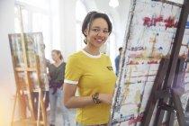 Портрет усміхнений жінка-художник живопис на мольберті у мистецтві клас студії — стокове фото