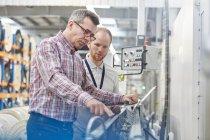Мужской надзиратель и рабочий осматривает машины на волоконно-оптическом заводе — стоковое фото