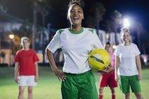 Portrait confident, laughing young female soccer player practicing on field at night — Stock Photo
