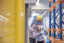 Мужчины и женщины-менеджеры с планшетом разговаривают на волоконно-оптической фабрике — стоковое фото