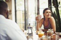 Улыбающаяся женщина пьет кофе за завтраком — стоковое фото