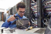 Male IT technician fixing equipment in server room — Stock Photo