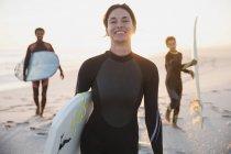 Портрет улыбающейся серфингистки в гидрокостюме, несущей доску для серфинга с семьей на солнечном летнем пляже — стоковое фото