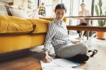 Female freelancer working at laptop, writing on paperwork in living room — Stock Photo
