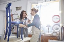 Smiling female artists painting chair blue in art class workshop — Stock Photo