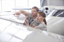 Инженеры-механики изучают крыло самолета в ангаре — стоковое фото