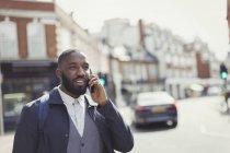 Businessman talking on cell phone on sunny urban street — Stock Photo