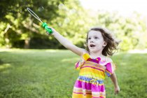 Preschool girl playing with bubble wand in summer yard — Stock Photo