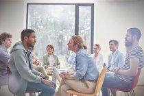 Група дивляться чоловік і жінка говорити лицем до лиця в групової терапії сесії — стокове фото