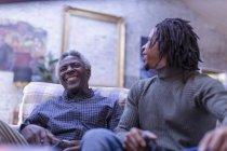 Großvater und Enkel lachen beim Videospiel auf dem Sofa — Stockfoto