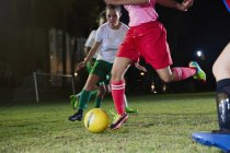 Young female soccer players playing on field at night, kicking the ball — Stock Photo