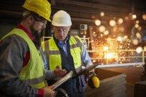 Руководитель и сталевар с планшетом разговаривают на сталелитейном заводе — стоковое фото