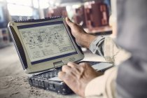 Engineer using laptop, reviewing blueprints in steel mill — Stock Photo