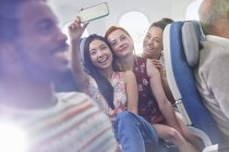 Young women friends with camera phone taking selfie on airplane — Stock Photo